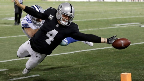 File-This Dec. 17, 2017, file photo shows Oakland Raiders quarterback Derek Carr (4) fumbling the ball into the end zone in front of Dallas Cowboys strong safety Jeff Heath (38) during the second half of an NFL football game in Oakland, Calif.  Carr would do it all over again: stretch the ball toward the goal line for a potential winning touchdown even knowing that the extra effort backfired and cost the Oakland Raiders a chance to win. (AP Photo/Ben Margot, File)