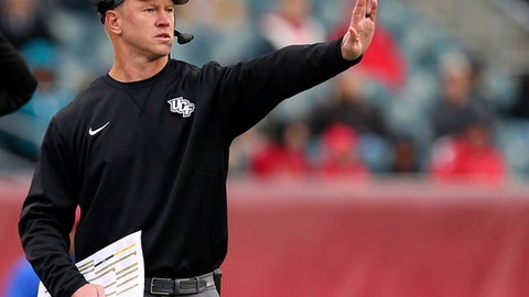 FILE - In this Saturday, Nov. 18, 2017, file photo, Central Florida head coach Scott Frost signals to his team during the third quarter of an NCAA college football game against Temple in Philadelphia. Frost and nine of his assistants will be full-time Nebraska employees immediately after the Peach Bowl game against Auburn on Monday, Jan. 1, 2018. Until then, they've worked almost nonstop to make sure the Central Florida players feel no disruption in their normal practice-day schedules. (AP Photo/Rich Schultz, File)
