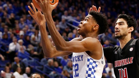 Kentucky's Shai Gilgeous-Alexander, left, shoots in front of Louisville's Anas Mahmoud (14) during the second half of an NCAA college basketball game, Friday, Dec. 29, 2017, in Lexington, Ky. Kentucky won 90-61. (AP Photo/James Crisp)