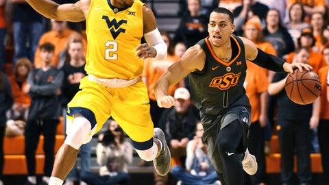 West Virginia guard Jevon Carter (2) races to catch up with Oklahoma State guard Kendall Smith (1) in the first half of an NCAA college basketball game in Stillwater, Okla., Friday, Dec. 29, 2017. (AP Photo/Brody Schmidt)