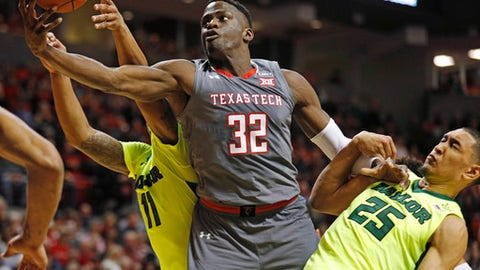 Texas Tech's Norense Odiase (32) rebounds the ball away from Baylor's Mark Vital (11) and Tristan Clark during the first half of an NCAA college basketball game Friday, Dec. 29, 2017, in Lubbock, Texas. (AP Photo/Brad Tollefson)