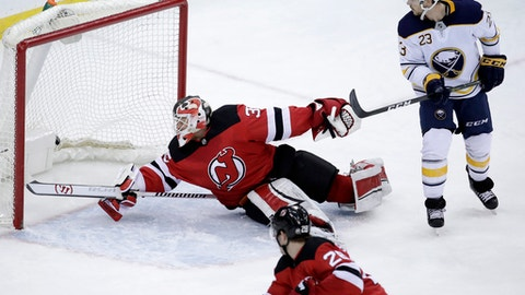 New Jersey Devils goalie Cory Schneider, center, dives but is unable to block a scoring shot by Buffalo Sabres center Jack Eichel, not pictured, during the third period of an NHL hockey game, Friday, Dec. 29, 2017, in Newark, N.J. Sabres' Sam Reinhart, right, and Devils' Damon Severson, bottom, look on during the play. The Devils won 4-3 in overtime. (AP Photo/Julio Cortez)