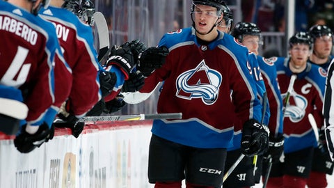Colorado Avalanche right wing Mikko Rantanen, front right, is congratulated after scoring a goal as he passes the team box during the second period of an NHL hockey game against the Toronto Maple Leafs on Friday, Dec. 29, 2017, in Denver. (AP Photo/David Zalubowski)