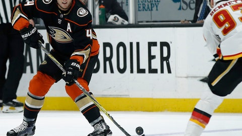 Anaheim Ducks defenseman Cam Fowler, left, passes the puck away from Calgary Flames center Sam Bennett, right, during the second period of an NHL hockey game in Anaheim, Calif., Friday, Dec. 29, 2017. (AP Photo/Alex Gallardo)