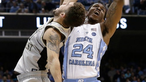 North Carolina's Kenny Williams (24) and Wake Forest's Mitchell Wilbekin reach for the ball during the first half of an NCAA college basketball game in Chapel Hill, N.C., Saturday, Dec. 30, 2017. (AP Photo/Gerry Broome)