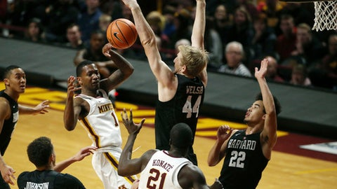Minnesota guard Dupree McBrayer (1) passes the ball to Minnesota center Bakary Konate (21) around Harvard forward Henry Welsh (44) as he drives to the basket in the first half of an NCAA college basketball game Saturday, Dec. 30, 2017, in Minneapolis. (Anthony Souffle/Star Tribune via AP)