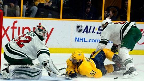 Nashville Predators forward Austin Watson (51) is taken down by Minnesota Wild center Mikko Kolvu (9) in front of Wild goalie Alex Stalock (32) in the second period of an NHL hockey game Saturday, Dec. 30, 2017, in Nashville, Tenn. (AP Photo/Mike Strasinger)
