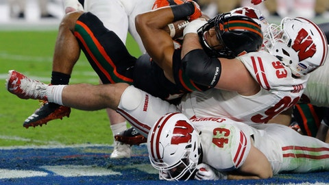 Wisconsin defensive end Garrett Rand (93) sacks Miami quarterback Malik Rosier (12), during the first half of the Orange Bowl NCAA college football game, Saturday, Dec. 30, 2017, in Miami Gardens, Fla. Under Rand is Wisconsin linebacker Ryan Connelly (43). (AP Photo/Joe Skipper)