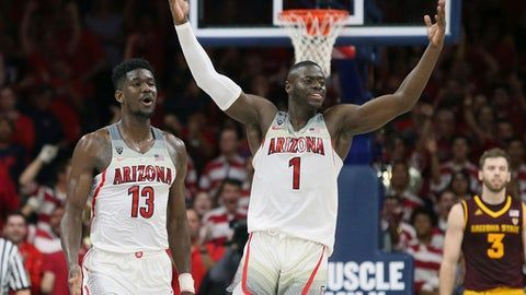 Arizona's Rawle Alkins (1) and Deandre Ayton (13) celebrate during the final seconds of the team's 84-78 victory over No. 3 Arizona State during an NCAA college basketball game, Saturday, Dec. 30, 2017, in Tucson, Ariz. (AP Photo/Ralph Freso)