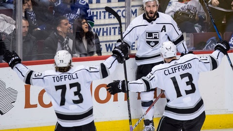 Los Angeles Kings' Drew Doughty, back right, celebrates his goal with Tyler Toffoli (73) and Kyle Clifford (13) against the Vancouver Canucks during the third period of an NHL hockey game Saturday, Dec. 30, 2017, in Vancouver, British Columbia. (Darryl Dyck/The Canadian Press via AP)