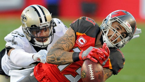 Tampa Bay Buccaneers wide receiver Mike Evans (13) can't hang onto a pass from quarterback Jameis Winston after getting past New Orleans Saints cornerback Marshon Lattimore (23) during the first half of an NFL football game Sunday, Dec. 31, 2017, in Tampa, Fla. (AP Photo/Steve Nesius)