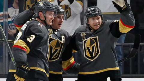 Vegas Golden Knights players celebrate after center William Karlsson, right, scored a hat trick against the Toronto Maple Leafs during the third period of an NHL hockey game, Sunday, Dec. 31, 2017, in Las Vegas. (AP Photo/John Locher)