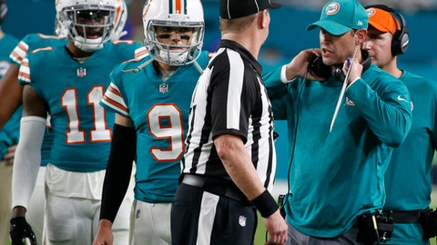 Miami Dolphins head coach Adam Gase talks to side judge Terry Brown after several players were ejected from the game, during the second half of an NFL football game against the Buffalo Bills, Sunday, Dec. 31, 2017, in Miami Gardens, Fla. To the left are Miami Dolphins quarterback David Fales (9) and wide receiver DeVante Parker (11). (AP Photo/Wilfredo Lee)