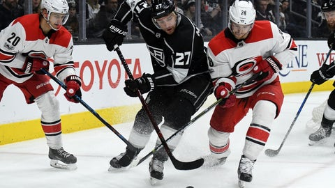 Dec 9, 2017; Los Angeles, CA, USA; Los Angeles Kings defenseman Alec Martinez (27) battles for the puck with Carolina Hurricanes center Elias Lindholm (28) and right wing Sebastian Aho (20) during an NHL hockey game at the Staples Center. The Kings defeated the Hurricanes 3-2 in overtime.  Mandatory Credit: Kirby Lee-USA TODAY Sports