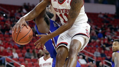 North Carolina State's Markell Johnson (11) passes the ball as Presbyterian's Reggie Dillard defends during the first half of an NCAA college basketball game in Raleigh, N.C., Thursday, Nov. 16, 2017. (AP Photo/Gerry Broome)
