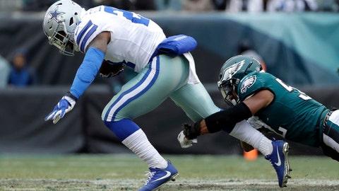 Dallas Cowboys' Ezekiel Elliott, left, is tackled by Philadelphia Eagles' Najee Goode during the first half of an NFL football game, Sunday, Dec. 31, 2017, in Philadelphia. (AP Photo/Michael Perez)