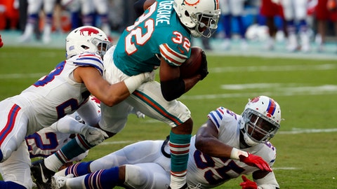 Buffalo Bills strong safety Micah Hyde (23) tackles Miami Dolphins running back Kenyan Drake (32), during the first half of an NFL football game, Sunday, Dec. 31, 2017, in Miami Gardens, Fla. To the right is Buffalo Bills defensive end Jerry Hughes (55). (AP Photo/Wilfredo Lee)