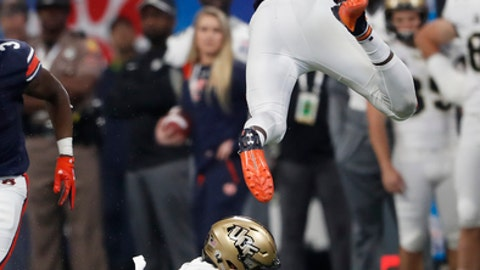 Auburn running back Kerryon Johnson leaps over Central Florida defensive back Mike Hughes during the first half of the Peach Bowl NCAA college football game Monday Jan. 1 2018 in Atlanta