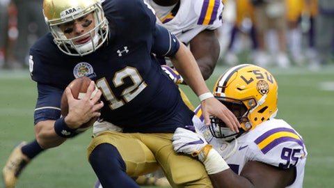 Notre Dame quarterback Ian Book (12) is sacked by LSU nose tackle Ed Alexander (95) during the first half of the Citrus Bowl NCAA college football game, Monday, Jan. 1, 2018, in Orlando, Fla. (AP Photo/John Raoux)