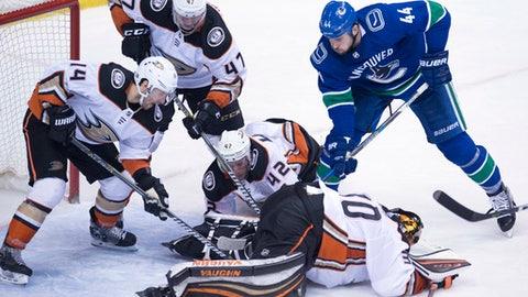 Anaheim Ducks' Josh Manson (42), Adam Henrique (14) and Hampus Lindholm (47) help goaltender Ryan Miller (30) contain the puck from Vancouver Canucks defenseman Erik Gudbranson (44)  during the third period of an NHL hockey game Tuesday, Jan. 2, 2018, in Vancouver, British Columbia. (Jonathan Hayward/The Canadian Press via AP)