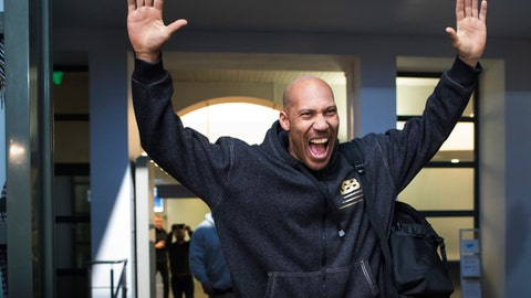 American basketball players LiAngelo and LaMelo's father LaVar Ball holds up his arms in greeting before speaking to the media upon their arrival at the international airport in Vilnius, Lithuania, Wednesday, Jan. 3, 2018. LiAngelo and LaMelo Ball in December signed one-year contracts to play for Lithuanian professional basketball club Prienai - Birstonas Vytautas from the small southern Lithuania town of Prienai, some 110 km (68 miles) of the Lithuanian capital Vilnius. (AP Photo/Mindaugas Kulbis)