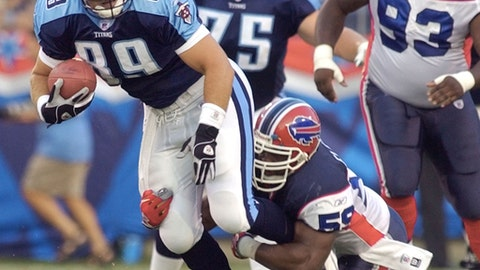 """FILE- In this Aug. 16, 2003, file photo, Tennessee Titans wide receiver Frank Wycheck (89) is brought down by Buffalo Bills linebacker London Fletcher (59) on the first play from scrimmage in the first quarter of their preseason game in Nashville, Tenn. Wycheck says he's glad the Bills have finally returned to the playoffs, 18 years after he threw the key lateral during a kickoff return that gave the Titans a playoff win over Buffalo in a play dubbed the """"Music City Miracle."""" (AP Photo/Mark Humphrey, File)"""