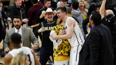 Colorado guard Lazar Nikolic, center, is overrun by fans as they celebrate by rushing the court after the team's NCAA college basketball game against Arizona State on pThursday, Jan. 4, 2018, in Boulder, Colo. Colorado won 90-81 in overtime. (AP Photo/David Zalubowski)
