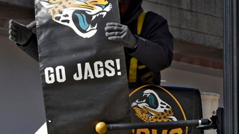 William Floyd, from PRI Productions, installs Jacksonville Jaguars banners on light poles along East Bay Street near the stadium in Jacksonville, Fla., Friday, Jan. 5, 2018. The Jaguars are to play the Buffalo Bills on Sunday in EverBank Field. (Bob Mack/The Florida Times-Union via AP)