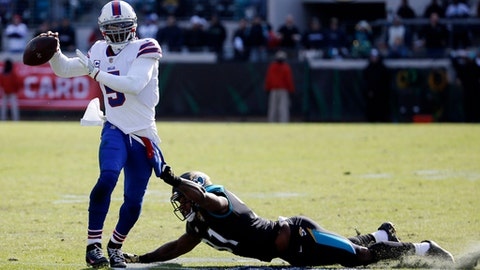 Jacksonville Jaguars defensive end Yannick Ngakoue, right, tries to stop Buffalo Bills quarterback Tyrod Taylor who scrambles from the pocket to throw a pass in the first half of an NFL wild-card playoff football game, Sunday, Jan. 7, 2018, in Jacksonville, Fla. (AP Photo/Stephen B. Morton)