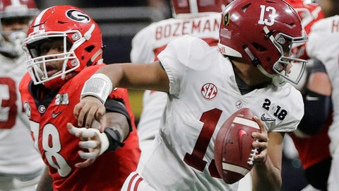 Alabama's Tua Tagovailoa scrambles from Georgia's Trenton Thompson during the second half of the NCAA college football playoff championship game Monday, Jan. 8, 2018, in Atlanta. (AP Photo/David J. Phillip)