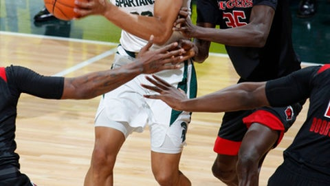 Michigan State's Miles Bridges, left, looks to pass against Rutgers' Issa Thiam during the first half of an NCAA college basketball game, Wednesday, Jan. 10, 2018, in East Lansing, Mich. (AP Photo/Al Goldis)