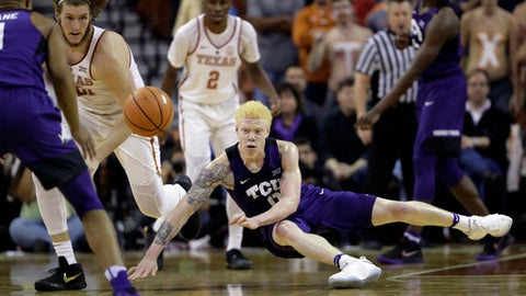 TCU guard Jaylen Fisher (0) and Texas forward Dylan Osetkowski (21) chase a loose ball during the second half of the team's NCAA college basketball game, Wednesday, Jan. 10, 2018, in Austin, Texas. Texas won in double overtime 99-98. (AP Photo/Eric Gay)