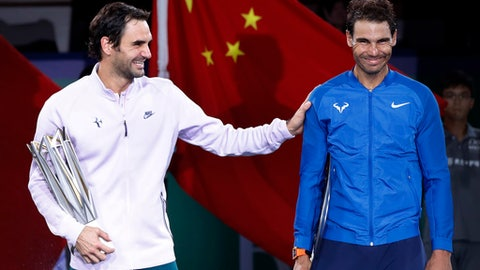 Roger Federer of Switzerland, left, gestures with Spain's Rafael Nadal after winning their men's singles final match in the Shanghai Masters tennis tournament at Qizhong Forest Sports City Tennis Center in Shanghai, China, Sunday, Oct. 15, 2017. (AP Photo/Andy Wong)