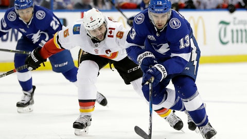 Tampa Bay Lightning center Cedric Paquette (13) gets around Calgary Flames defenseman Mark Giordano (5) during the second period of an NHL hockey game Thursday, Jan. 11, 2018, in Tampa, Fla. (AP Photo/Chris O'Meara)