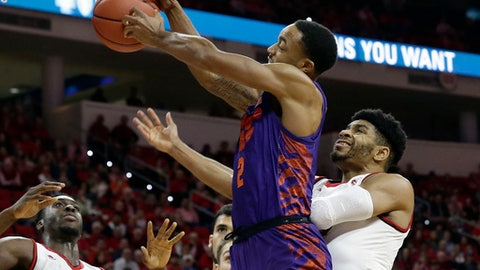 Clemson's Marcquise Reed (2) drives to the basket while North Carolina State's Abdul-Malik Abu, left, and Allerik Freeman defend during the first half of an NCAA college basketball game in Raleigh, N.C., Thursday, Jan. 11, 2018. (AP Photo/Gerry Broome)