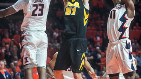 Iowa forward Nicholas Baer (51) goes up with a shot between Illinois guard Aaron Jordan (23) and forward Greg Eboigbodin (11) during overtime of an NCAA college basketball game in Champaign, Ill., Thursday, Jan. 11, 2018. Iowa won 104-97 in overtime. (AP Photo/Rick Danzl)