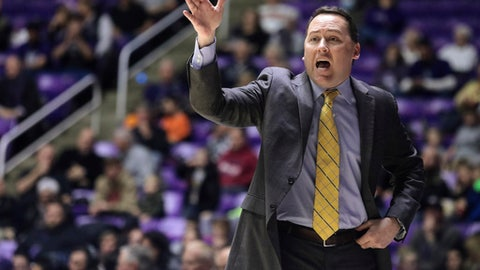 FILE - In this Jan. 4, 2018, file photo, Northern Arizona coach Jack Murphy calls to his team during the first half of an NCAA college basketball game against Weber State, in Ogden, Utah. High-major college basketball programs fly on chartered jets, stay in upscale hotels and eat at nice restaurants. The smallest of the 351 schools in Division I fly coach, look for hotel and meal deals and are forced to catch early-morning flights the day after games to get back to school. The difference in travel arrangements takes a toll. (Matt Herp/Standard-Examiner via AP, File)