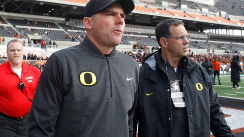 FILE - In this Nov. 26, 2016, file photo, Oregon head football coach Mark Helfrich, foreground, walks onto the field before an NCAA college football game against Oregon State, in Corvallis, Ore. Oregon fired coach Mark Helfrich Tuesday night, Nov. 29, 2016, after a disappointing 4-8 season, and just two years after getting the Ducks within a victory of the program's first national championship. (AP Photo/Timothy J. Gonzalez, file)