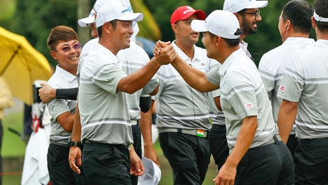 Hideto Tanihara of Japan, left, and Kang Sung-hoon of South Korea, right, celebrate winning the foursome matches during the 2018 EurAsia Cup golf tournament at Glenmarie Golf & Country Club in Shah Alam, Malaysia, Saturday, Jan. 13, 2018. (AP Photo/Sadiq Asyraf)