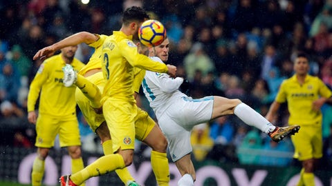 Real Madrid's Gareth Bale, centre and Villarreal's Alvaro Gonzalez go for a header in the goalmouth during a Spanish La Liga soccer match between Real Madrid and Villarreal at the Santiago Bernabeu stadium in Madrid, Spain, Saturday, Jan. 13, 2018. (AP Photo/Paul White)