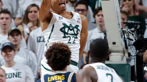 Michigan State's Miles Bridges (22) dunks over Michigan's Isaiah Livers (4) as Michigan State's Jaren Jackson Jr. (2) watches during the first half of an NCAA college basketball game, Saturday, Jan. 13, 2018, in East Lansing, Mich. (AP Photo/Al Goldis)