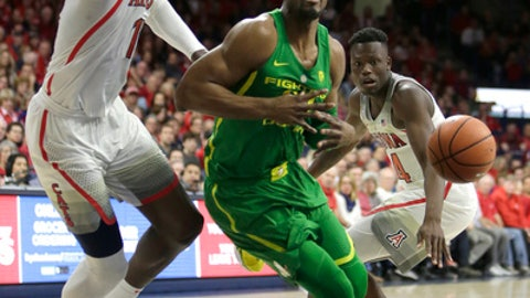 Oregon forward Paul White (13) gets fouled by Arizona forward Deandre Ayton, left, in the first half during an NCAA college basketball game, Saturday, Jan. 13, 2018, in Tucson, Ariz. (AP Photo/Rick Scuteri)
