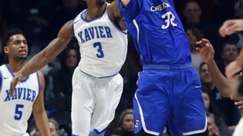 Creighton's Toby Hegner (32) rebounds against Xavier's Quentin Goodin (3) in the first half of an NCAA college basketball game, Saturday, Jan. 13, 2018, in Cincinnati. (AP Photo/John Minchillo)