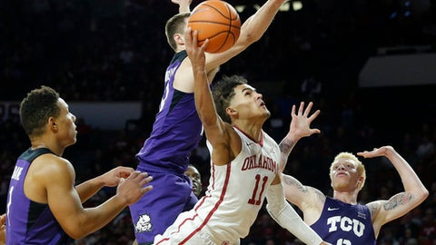 Oklahoma's Trae Young (11) makes a shot against TCU's Desmond Bane (1), Vladimir Brodziansky (10) and Jaylen Fisher (0) during the second half of an NCAA college basketball game in Norman, Okla., Saturday, Jan. 13, 2018. (AP Photo/Garett Fisbeck)