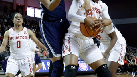Connecticut forward Azura Stevens (23) reaches over Houston forward Octavia Barnes (2) for a rebound during the first half of an NCAA college basketball game Saturday, Jan. 13, 2018, in Houston, Texas. (AP Photo/Michael Wyke)