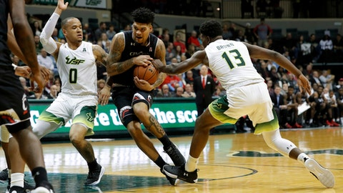 Cincinnati's Jarron Cumberland, center, tries to split the defense of South Florida's Stephan Jiggetts, left and Justin Brown, right, during the first half of an NCAA college basketball game Saturday, Jan. 13, 2018, in Tampa, Fla. (AP Photo/Mike Carlson)