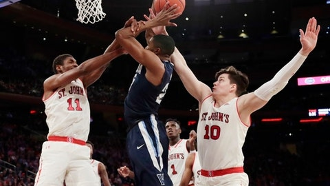 St. John's Tariq Owens (11) and Amar Alibegovic (10) defend Villanova's Mikal Bridges during the first half of an NCAA college basketball game Saturday, Jan. 13, 2018, in New York. (AP Photo/Frank Franklin II)