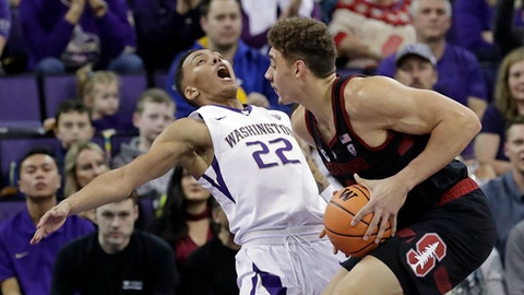 Washington's Dominic Green (22) tumbles backward after colliding with Stanford's Reid Travis in the first half of an NCAA college basketball game Saturday, Jan. 13, 2018, in Seattle. (AP Photo/Elaine Thompson)