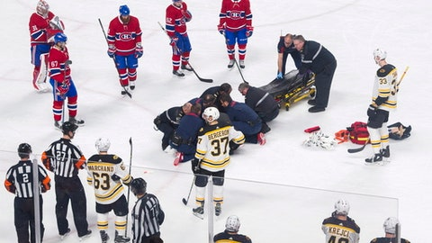 Players from the Montreal Canadiens and Boston Bruins look on as Canadiens' Phillip Danault tended to by paramedics after he was hit in the head by a puck on a shot by Bruins' Zdeno Chara (33) during second period NHL hockey action in Montreal, Saturday, Jan. 13, 2018. (Graham Hughes/The Canadian Press via AP)