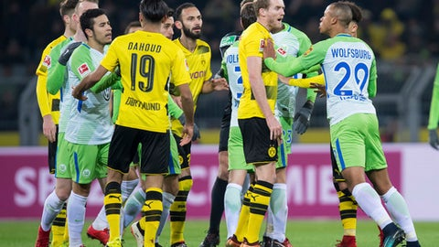Wolfsburg's Marcel Tisserand, right, and Dortmund's Andre Schurrle, 2nd right, face off at the German Bundesliga soccer match between Borussia Dortmund and VfL Wolfsburg, in Dortmund, Germany, Sunday, Jan. 14, 2018. (Guido Kirchner/dpa via AP)
